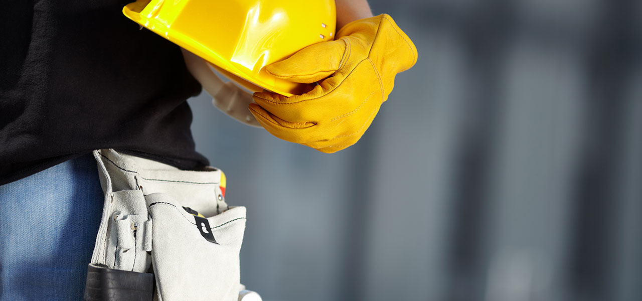 A side on close up of a blue collar worker kitted out