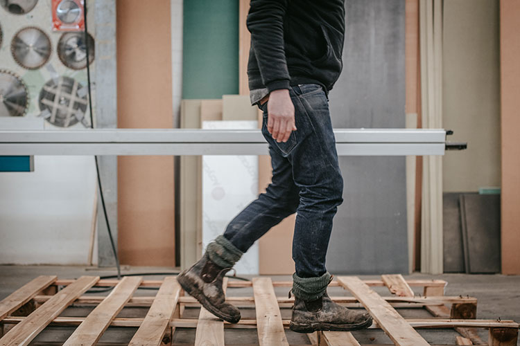 worker walking on a wooden pallet