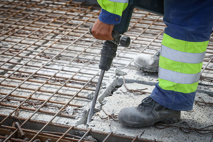 worker with jackhammer on concrete