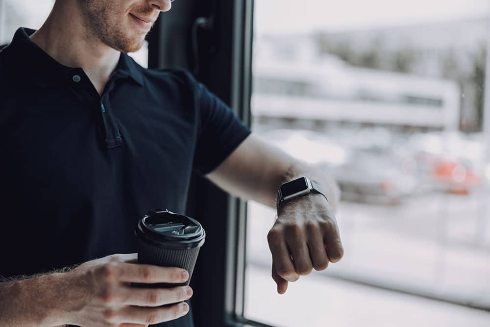 man with coffee at work in polo