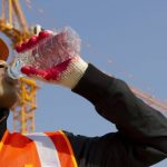 Construction worker drinking water from bottle.