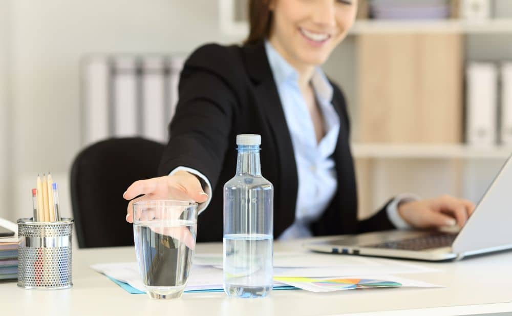 Office worker reaching for water in a glass.